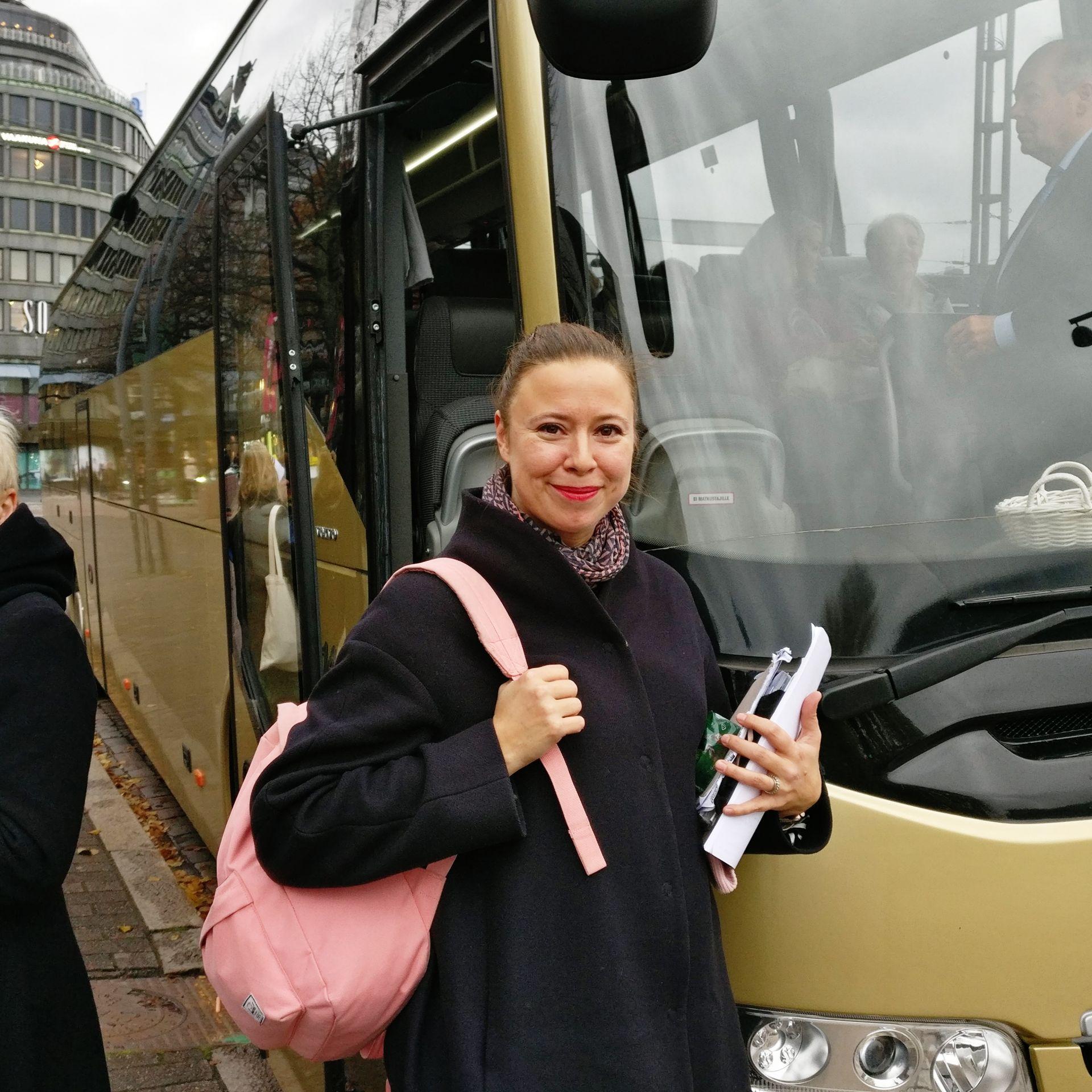 Kvinna i 30-40 års åldern med rosa ryggsäck som står framför en buss.