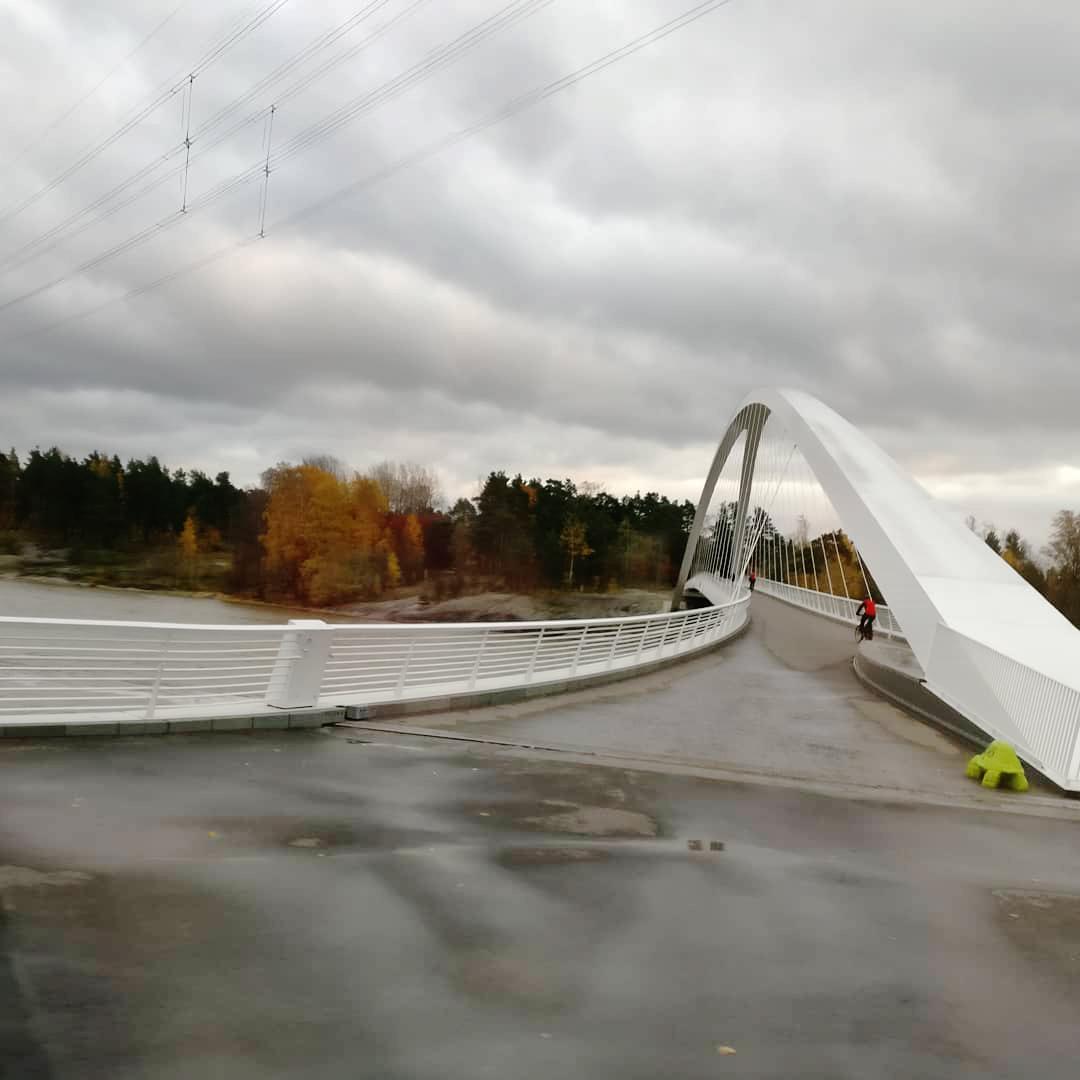 Vit modern gångbro som leder till Blåbärslandet, i bakgrunden.