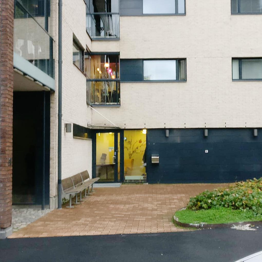 Höghusfasad med glasdörr med ingång från gatunivå. Ett träd är målat på en gul vägg på insidan.
